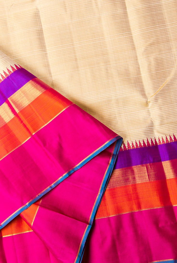 SUBTLE BEIGE HAS COMPLIMENTING STRIKING DARK PINK, ORANGE AND VIOLET TEMPLE BORDER. THE DARK PINK WITH GOLD ZARI PALLU ADD BEAUTY TO THIS SAREE.