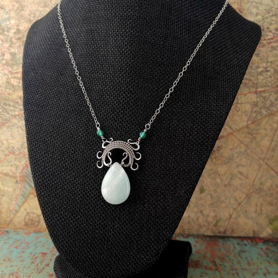 Lyonesse is a rustic fine silver wire-wrapped pendant with a beautiful Amazonite teardrop seamlessly suspended in a hand forged and intricately woven frame. This piece is named after the lost island of Lyonesse from Arthurian legend because the graceful curls of the woven pendant frame remind me of waves closing in over a receding island. The elegant lines of this design allow the focal stone to take center stage while the wire wrapped frame adds just the right amount of texture and…