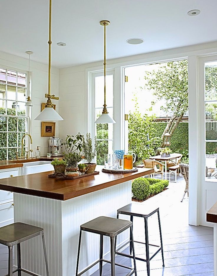 COCOCOZY: OLD KITCHEN MADE NEW - 5 REMODELING TIPS - Olivia Brock Lacquered Life Charleston Kitchen in white brass with butcher block counters, pine wood floors laid on the diagonal, indoor outdoor garden view