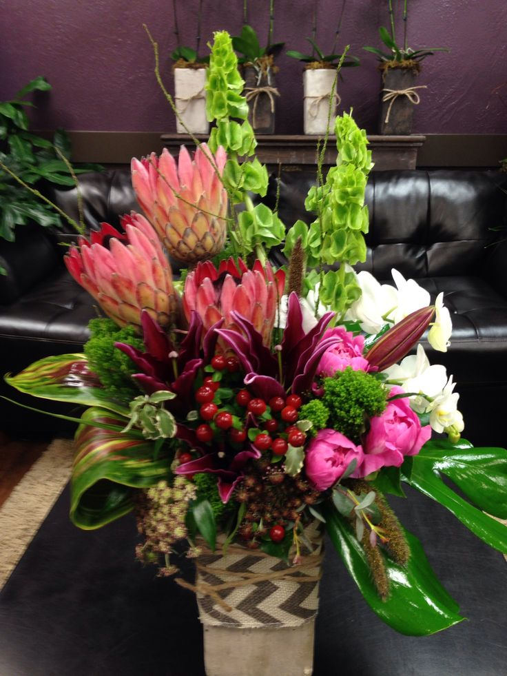 Tropical floral arrangement with Protea, Orchids, peonies, Belles of Ireland, and Ti leaves.