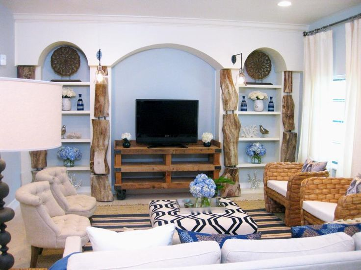 This blue-and-white living room features an eclectic mix of stylish coastal decor. The beach-inspired space brings the outdoors in with driftwood-lined bookshelves and soft blue walls.