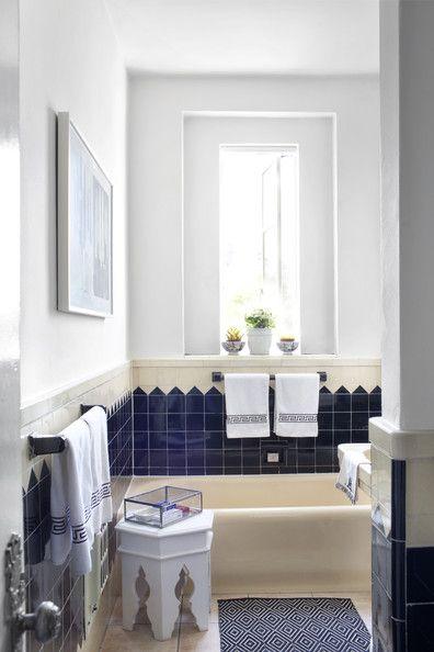 Eclectic Bathroom - A bathroom with tiled walls, an ikat bath mat, and a Moroccan stool / Burnham Design