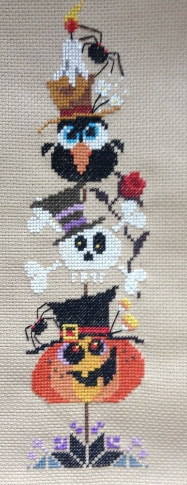 completed cross stitch Halloween stuccoed up pumpkin, skeleton spiders and crows