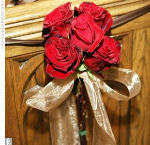 Inside the cathedral, pew markers were made of deep red Black Magic roses and tied with champagne ribbon.