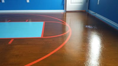 Final Shot of my daughter's floor after all the steps have been completed.  Plywood has been sanded, filled, and sanded again until smooth.  We then added 3 coats of primer and 2 coats of paint, followed by gel stain for wood texture, wood stain for color, and of course, painted in court lines for the overall look.  To top it off we gave it 3 coats of polyurethane and this is the result!  Follow along to see how we did it!