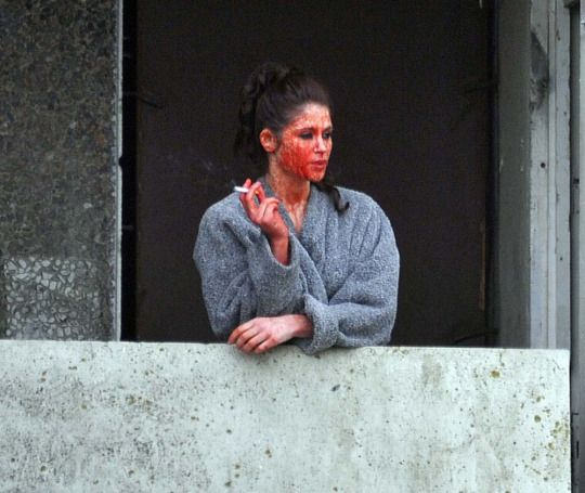Actress Gemma Arterton on a break during the filming of 'Byzantium'. She went out to the balcony for a smoke and forgot to clean the fake blood off her face. Awesome.