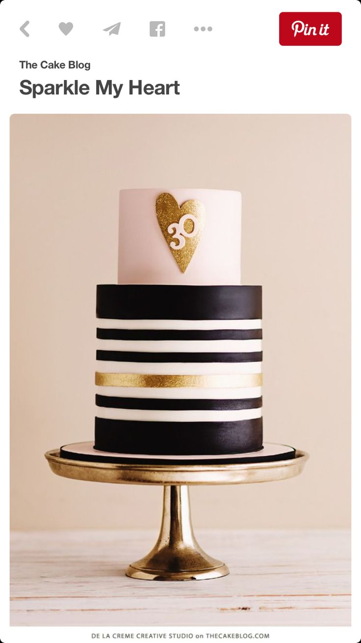 Two tier, tall black, gold, white striped cake with heart detail.