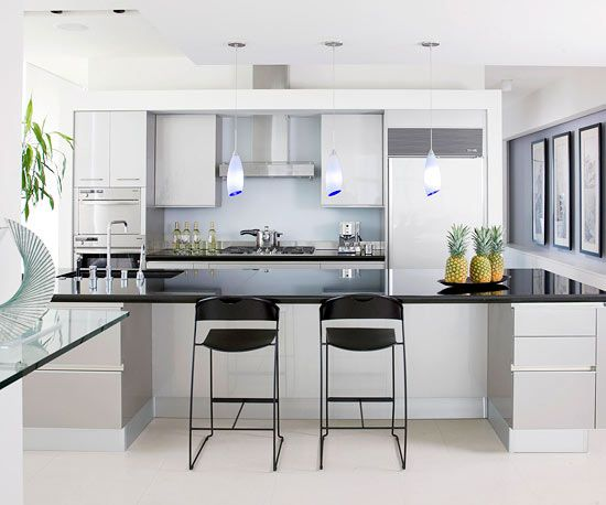 Reflective and skylike, this sleek kitchen blends pewter-color cabinets with honed-black-granite countertops. An etched-glass backsplash marries well with contemporary built-ins and sculptural pendant fixtures.