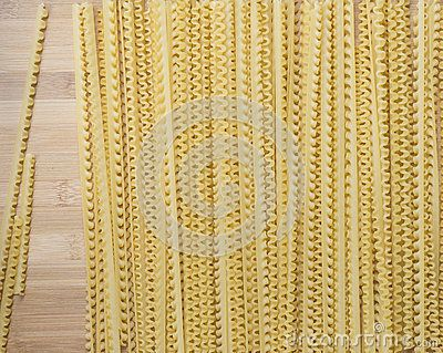 Lengths of pasta lay on a wooden board.