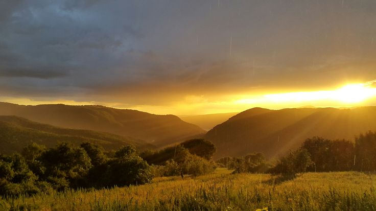 Dramatic golden sunset over the Tiber Valley with rain drops like liquid gold. Umbria, Italy. Photo by Caroline van Agteren