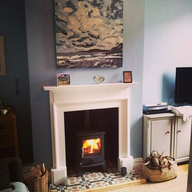Lounge: wood burner, painted mantelpiece and tiled hearth