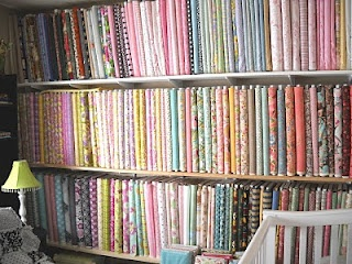 Shelving for Fabric Bolts... wow! I hope my sewing room looks that neat and organized when I'm done!