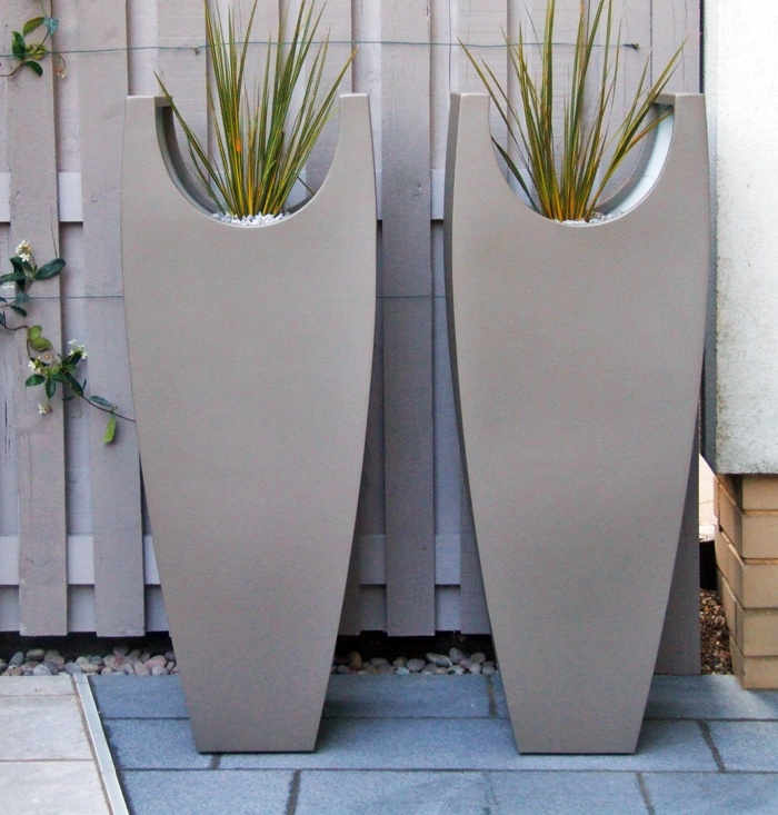 A pair of tall #curved #vases with Libertia grasses in a #contemporary Highbury courtyard. Powder coated steel planters with a sable textured exterior and smooth white interior.
