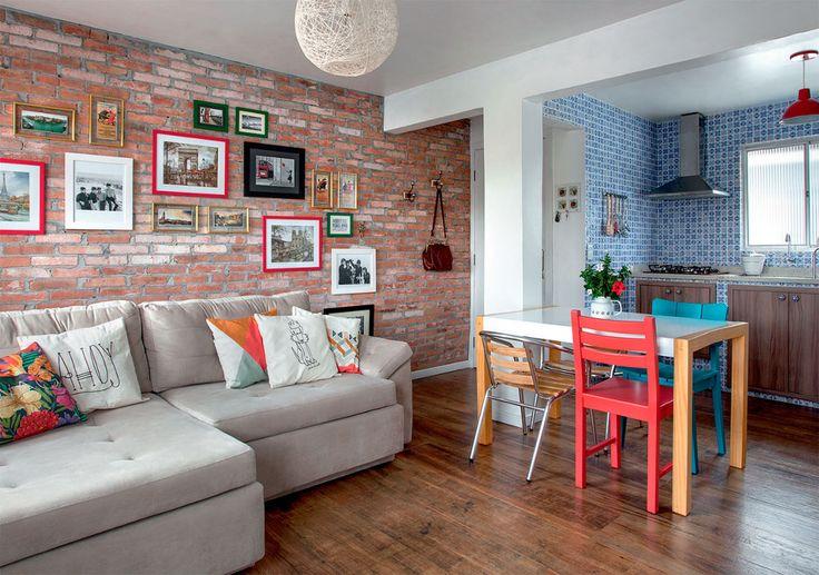 - parede de tijolos com quadrinhos de diferentes tamanhos - mesa com cadeiras diferentes - almofadas coloridas