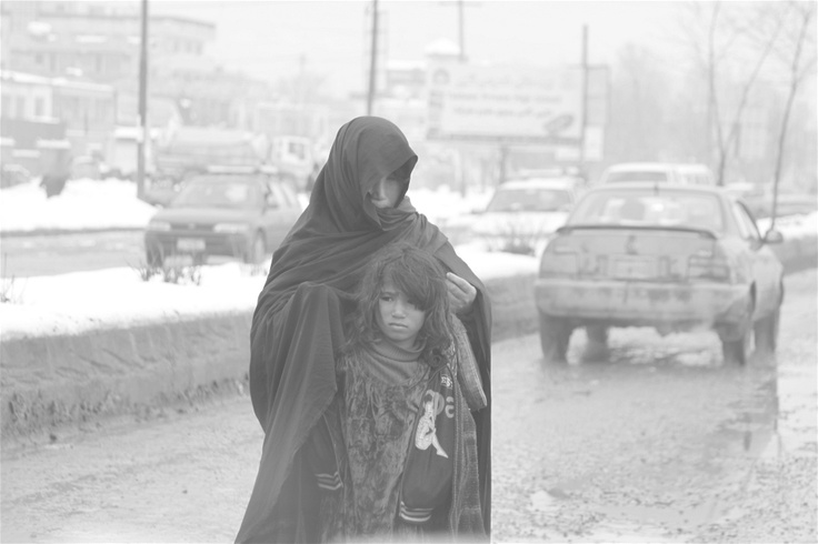 An Afghan mother and her daughter begging on a street in Kabul