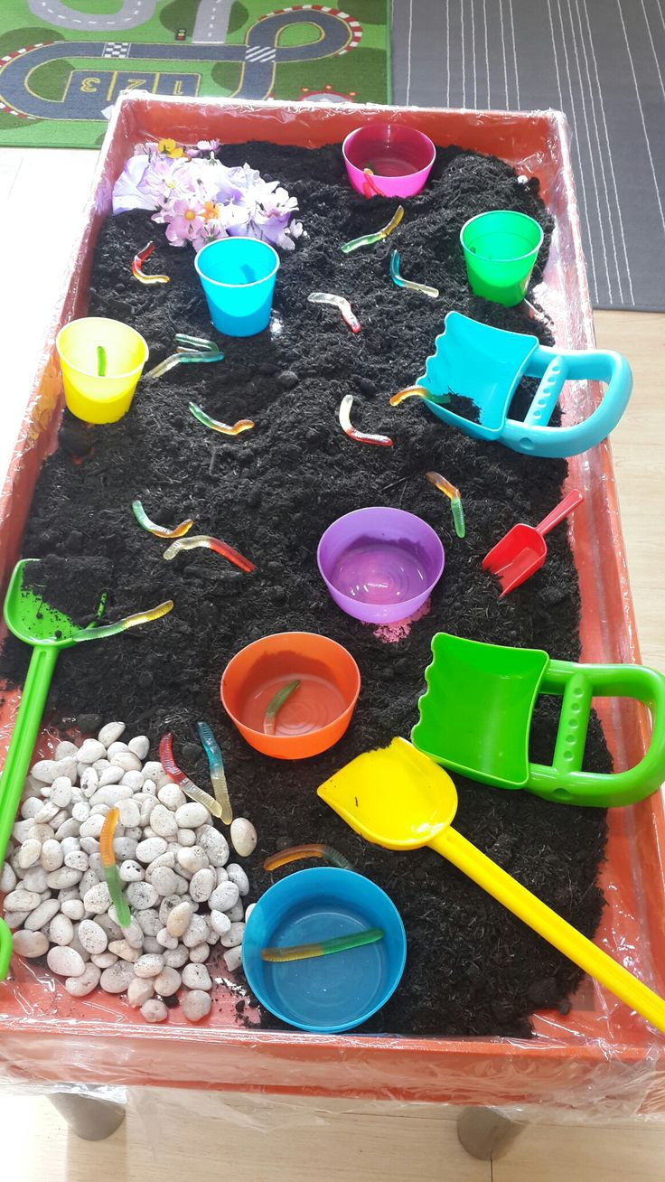Garden sensory table.  What you'll need: soil, pebbles,  flowers, spades and containers, and some candy worms.