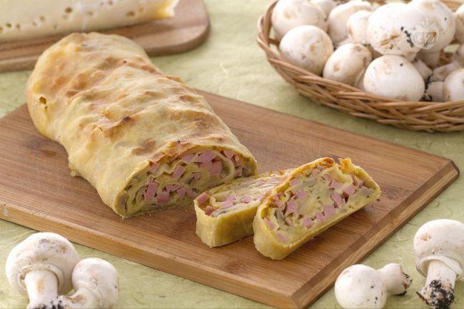 Lo strudel salato con prosciutto, funghi e fontina è realizzato con un morbido impasto  e un goloso ripieno di funghi, fontina e cubetti di cotto.