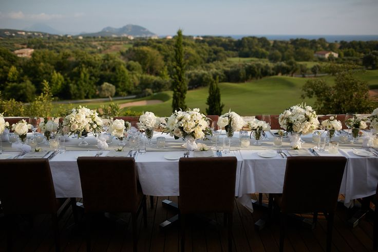 The wedding table filled with crystal vases with the white flower compositions of peonies, roses and a touch of wild greenery to match the surroundings.