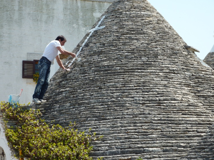 Painting Symbols On The Trulli House Roof To Keep The Evil