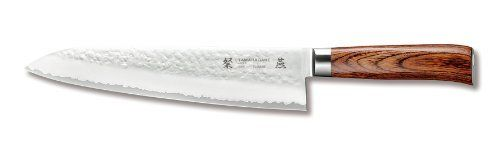 "Tamahagane San Tsubame Wood SNH-1104 - 10 inch, 240mm Chef's Knife by Tamahagane. $189.95. 3-Ply stainless steel with VG-5 center and the outside layers of SUS410SS. The angle of the edge is 14 to15-Degree and 61-Degree on the rockwell scale for hardness. Manufactured by Kataoka and Company in Niigata, Japan. Dark laminated wood, hand hammered and sandblasted for a matte finish. The word Tamahagane means ""precious steel"". The Tamahagane San Tsubame hand-ha-mmere..."