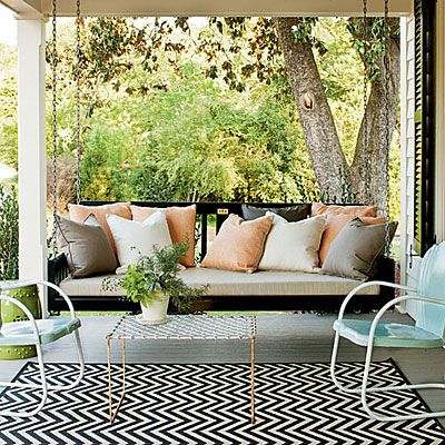 Elegant Black Porch Swing | This classic porch features a comfortable bed-style swing. Clear the calendar—once you take the first swing, you'll be here for hours. | SouthernLiving.com
