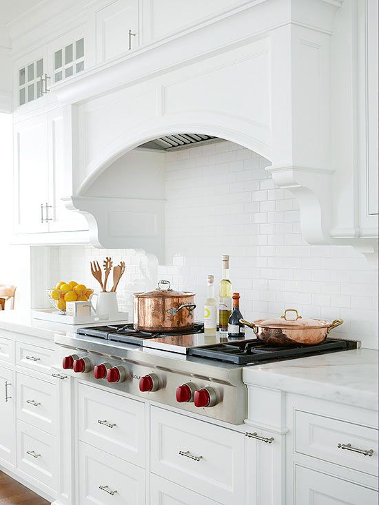 A substantial arch on this range hood presents a classic look. Custom moldings bring even more visual interest, while allowing the hood to meld with the cabinetry.