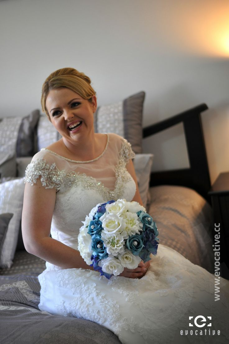 Alison the bride sitting on her bed with her flower bouquet. #WeddingPhotography