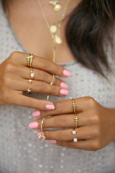 Pink nails and gold rings.