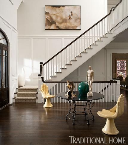 A lofty, two-story foyer presents an eclectically curated art selection. - Traditional Home ® / Photo: John Bessler / Design: Michael Herold