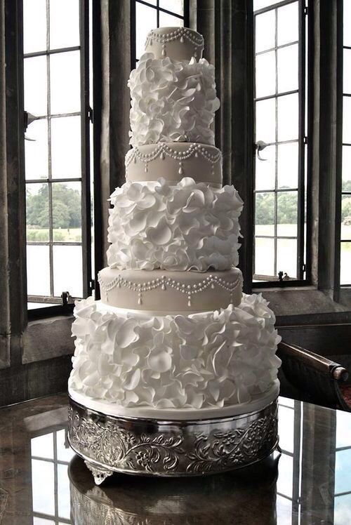 A wedding cake with Regal white petals and pearls. How beautiful & yummy-looking.
