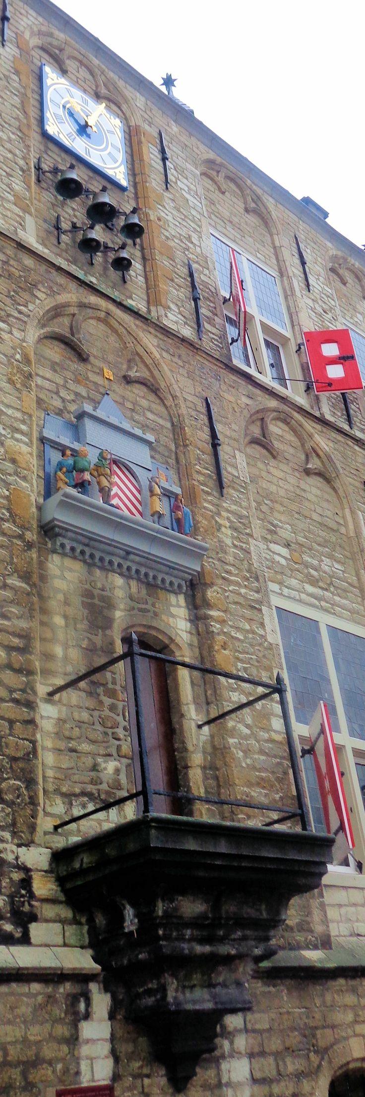 De oostgevel bevat een schitterend uurwerk, gerestaureerd in 1996, met een bewegende voorstelling van graaf Floris V die Gouda de stadsrechten overhandigt. Het poppenspel, dat elk half uur speelt, werd in 1961 geschonken door Geert Bouwmeester, oprichter van de Goudse Verzekeringen en ereburger van Gouda. Onder het carillon bevindt zich een klein balkonnetje, dat ook wel een hangende kaak werd genoemd. Hier werden veroordeelden van lichte vergrijpen openbaar aan de kaak gesteld.
