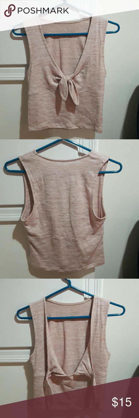 Tie-front Tank Top A cute powder pink top for warm weather! The front can be tied and untied easily. Its length is between that of a crop top and a normal top, meaning it tends to show a little belly. (;  Great quality. Soft. Little to no signs of wear.  tags; girly summer summery teen vacay vacation beachy beach scoop neck low cut American Eagle Outfitters Tops Tank Tops