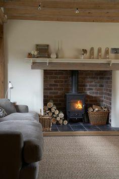 tapis sisal, cheminée rustique, plafond en bois et sofa gris
