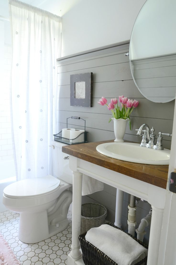 Neutral style small bathroom with gray shiplap and pedestal sink.