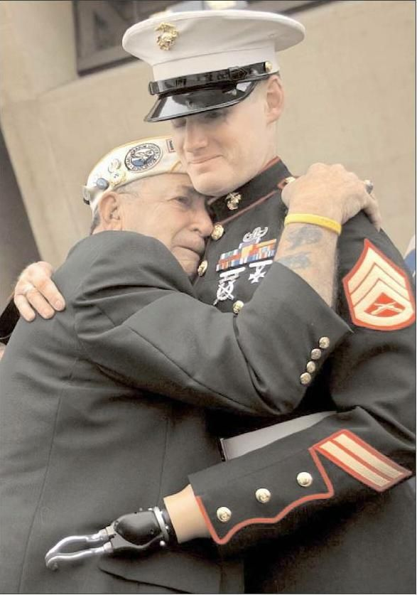 Pearl Harbor survivor Hudson James embraces SSGT Mark Graurke Jr. who lost his hand and eye while attempting to defuse a bomb in Iraq