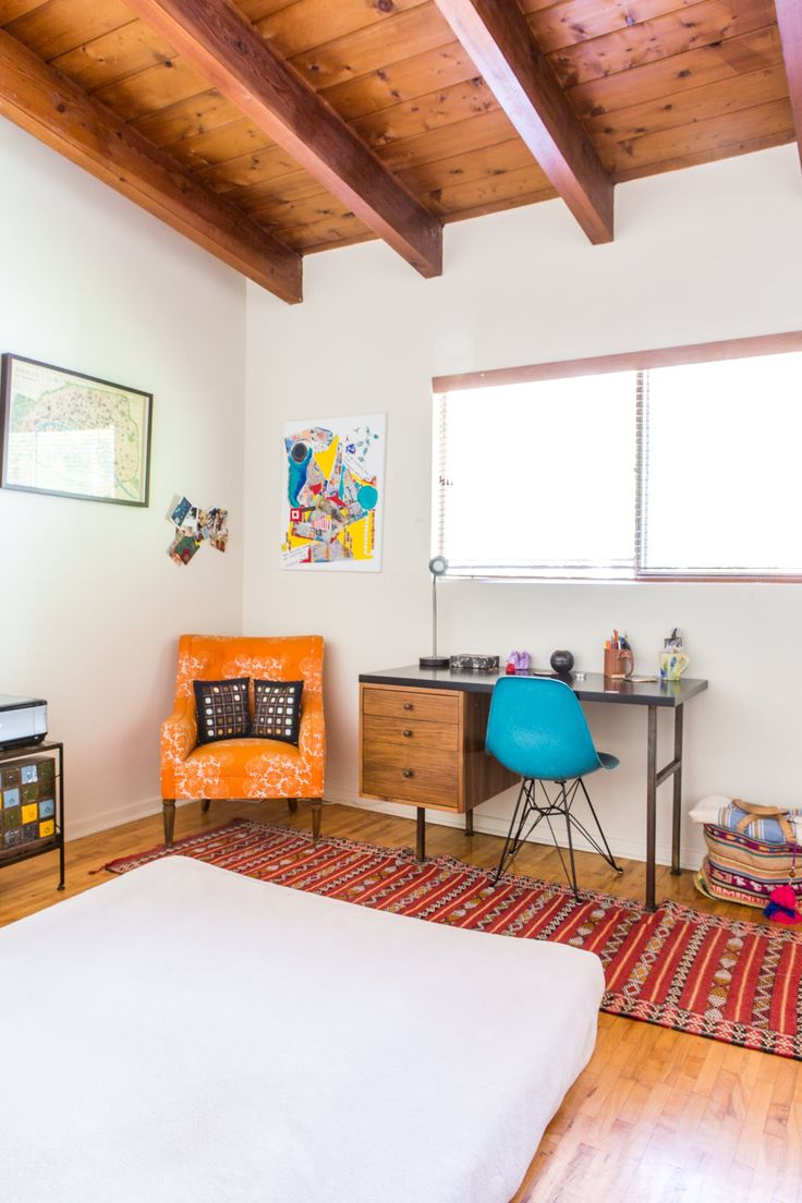 The guest room is filled with colorful items like the rug from Morocco. The desk is from Galerie Sommerlath.