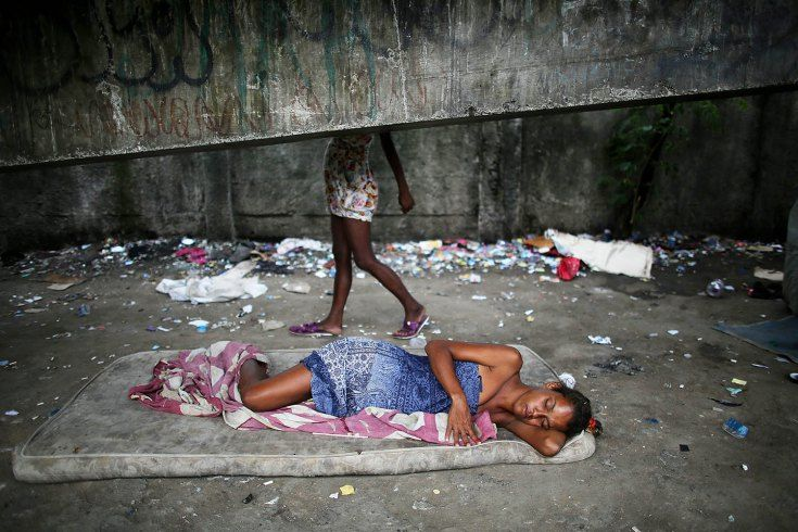 Dec. 10, 2013. Drug users gather beneath an overpass in an area known as 'Cracolandia', or Crackland, in the Antares shantytown in Rio de Janeiro, Brazil.