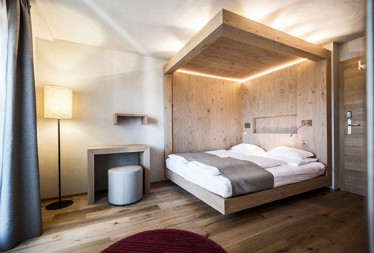 Originale camera da letto con baldacchino in legno - l'illuminazione a Led inserita nella parte alta e due applique collocate lateralmente - semplice ma di grande effetto