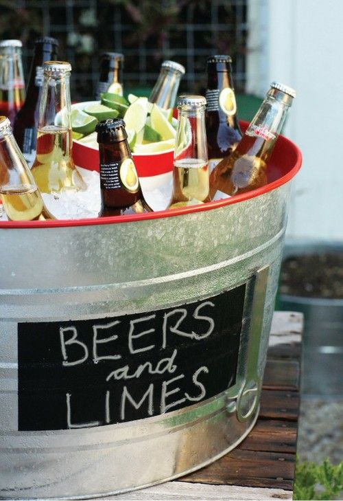 Casual and fun way to serve beer. Love the addition of limes to the bucket.