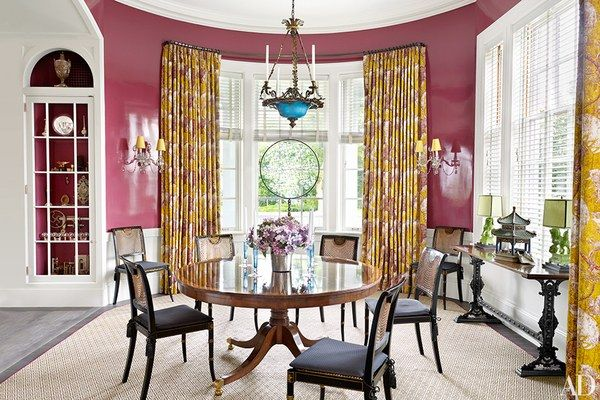 Anchoring the dining room of the Millbrook, New York, weekend home of architect Peter Pennoyer and designer Katie Ridder is a Regency-style pedestal table acquired at Doyle New York, while the Regency-style chairs and 19th-century French console are from Stair Galleries; the curtains are of a John Stefanidis print, the blinds are by Levolor, and the wall color is by Fine Paints of Europe.