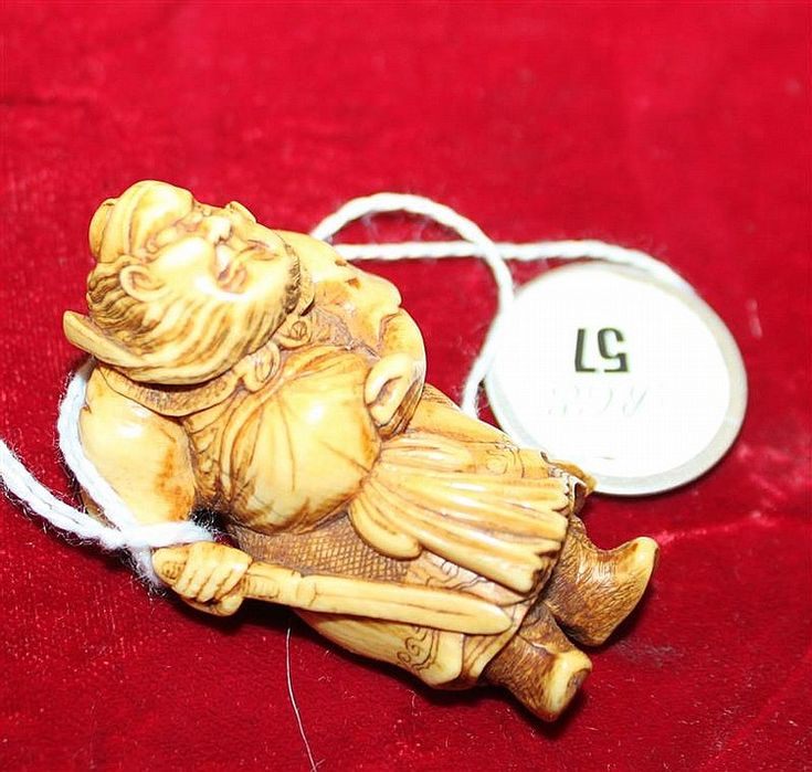 IVORY NETSUKE In the form of Shoki standing with a drawn swo