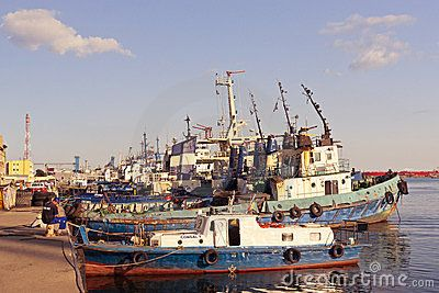 BLACK SEA, CONSTANTA, ROMANIA - AUGUST 03, 2011 - Sailor fishes from the port berth edge on August 03 2011 in Constanta port. Many anchored towboats nearby.