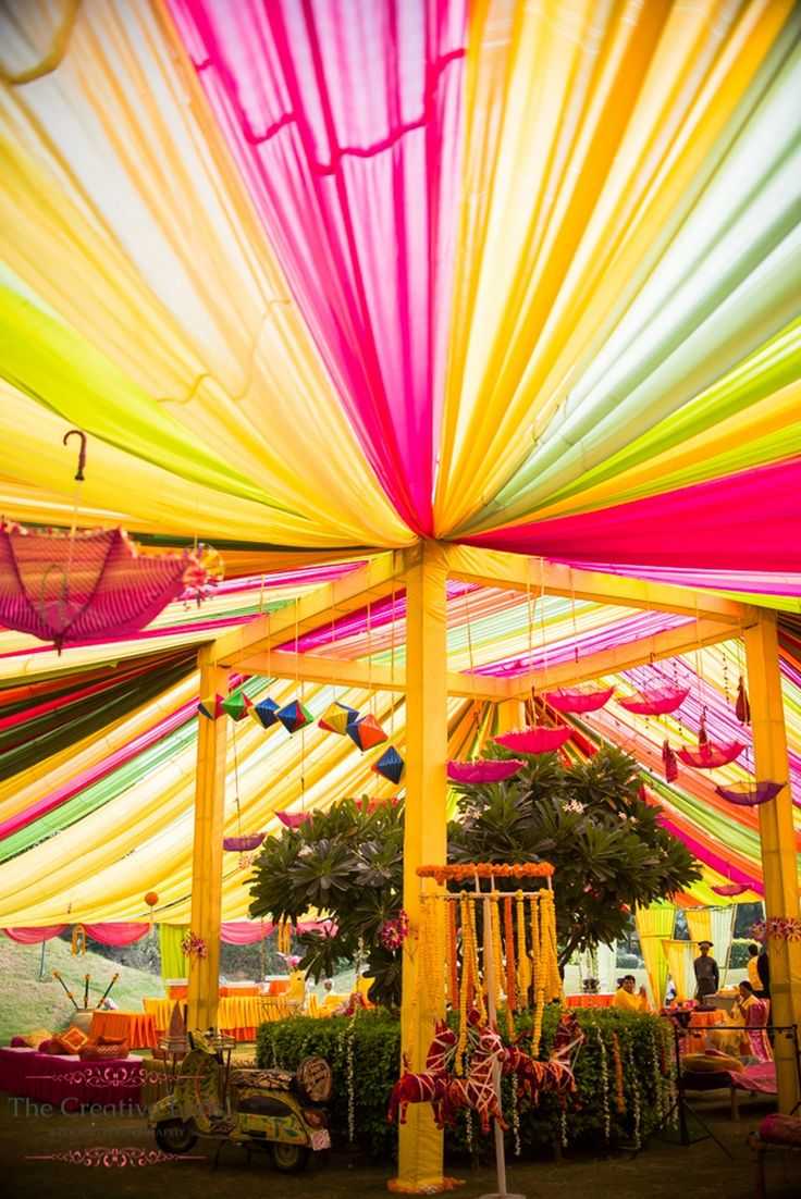 Mehendi function decor with bright Colourful Draps umbrella and scooter | weddingz.in | India's Largest Wedding Company | Wedding Venues, Vendors and Inspiration | Indian Wedding Bridal Jewellery Ideas |