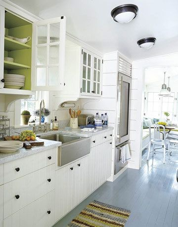 Love the farm sink, painted floors and white cabinets.  And love the inside of the cupboard painted in a bright colour. Not the beadboard for the cabinets though; too hard to keep clean.
