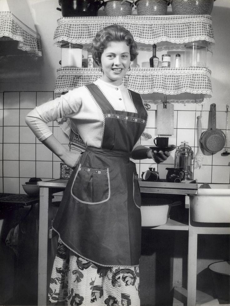 Een huisvrouw met schort aan poseert trots in haar keuken met een kopje en schotel in de hand, Nederland, jaren '50.. theetime