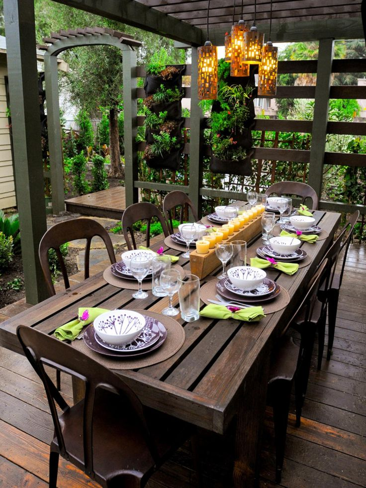 Designer Jamie Durie created this outdoor dining room for a California couple who were eager to combine two passions: gardening and entertaining. A pergola provides shade and gives this outdoor space a secluded feel while a wall covered in edible-plant-filled pouches puts fresh veggies within easy reach so guests can help themselves.