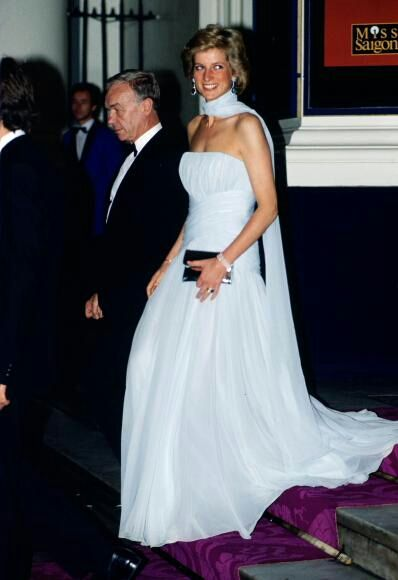 Diana, Princess of Wales attends the Cannes film festival wearing a pale blue chiffon dress and wrap designed by fashion designer Catherine Walker.