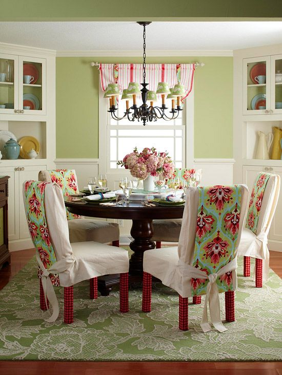Sage + Raspberry   In this charming dining room, walls are a quiet sage, which provides a nearly neutral background along with the white wainscoting and corner cabinets. Complementary red, with a hint of turquoise, is green?s color companion in accents and fabrics. Panels of brightly colored fabric drape slipcovered dining chairs. At the window, coordinating green-and-raspberry striped fabric gathers with the help of contrasting fabric strips that match the chairs.