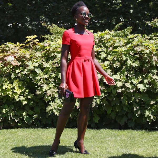 Lupita Nyong'o de Stars at Paris Haute Couture Fashion Week Fall 2015  Red hot indeed! The actress stuns in cheery red frock at the Christian Dior show.