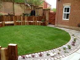 Small circular lawn defined by a curved gravel planting bed and a vertical timber wall and built in bench.